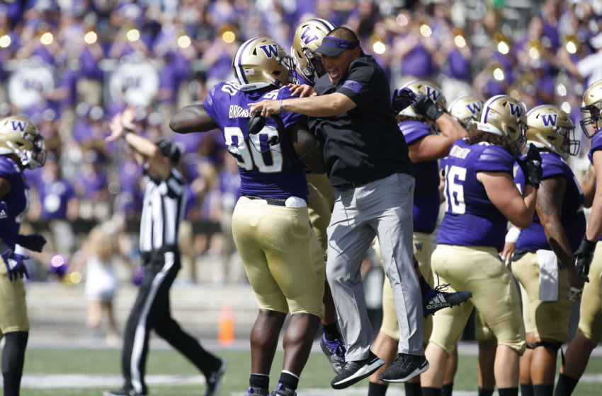 Aug 31, 2019; Seattle, WA, USA; Washington Huskies defensive lineman Josiah Bronson (90) celebrates with defensive line coach Ikaika Malloe after a stop against the Eastern Washington Eagles during the first quarter at Husky Stadium. Mandatory Credit: Jennifer Buchanan-USA TODAY Sports