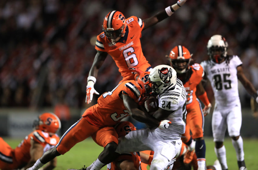 RALEIGH, NORTH CAROLINA - OCTOBER 10: Eric Coley #34 of the Syracuse Orange hits Zonovan Knight #24 of the North Carolina State Wolfpack during their game at Carter Finley Stadium on October 10, 2019 in Raleigh, North Carolina. (Photo by Streeter Lecka/Getty Images)