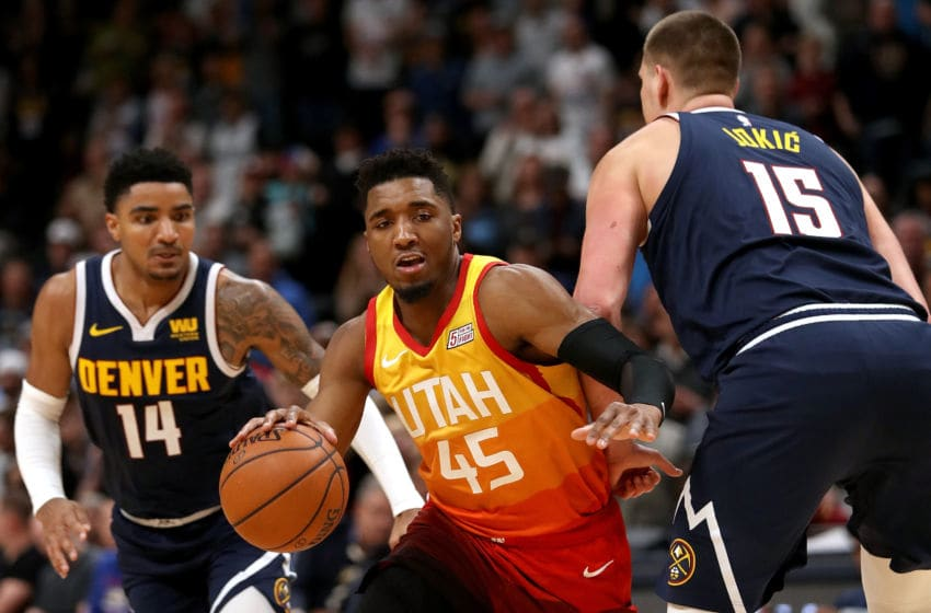 DENVER, COLORADO - FEBRUARY 28: Donovan Mitchell #45 of the Utah Jazz drives against Gary Harris #14 and Nikola Jokic #15 of the Denver Nuggets in the fourth quarter at the Pepsi Center on February 28, 2019 in Denver, Colorado. (Photo by Matthew Stockman/Getty Images)