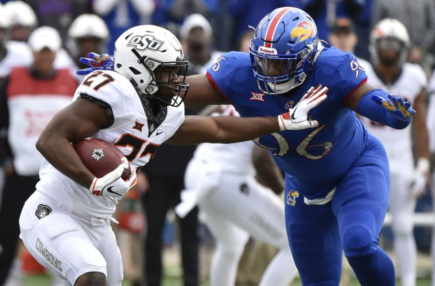 LAWRENCE, KS - SEPTEMBER 29: Running back J.D. King #27 of the Oklahoma State Cowboys looks to rush against defensive tackle Daniel Wise #96 of the Kansas Jayhawks in the first quarter at Memorial Stadium on September 29, 2018 in Lawrence, Kansas. (Photo by Ed Zurga/Getty Images)
