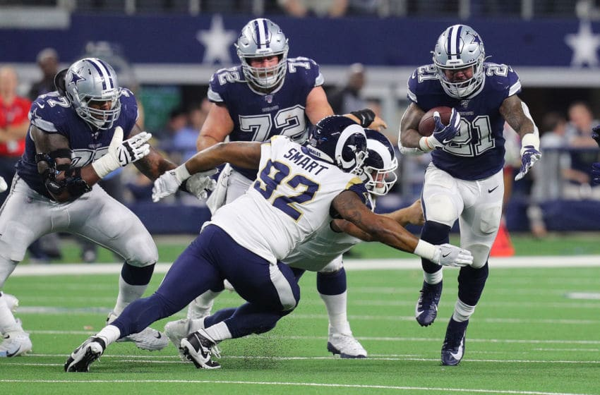 ARLINGTON, TEXAS - DECEMBER 15: Tanzel Smart #92 of the Los Angeles Rams tries to stop the run by Ezekiel Elliott #21 of the Dallas Cowboys at AT&T Stadium on December 15, 2019 in Arlington, Texas. (Photo by Richard Rodriguez/Getty Images)