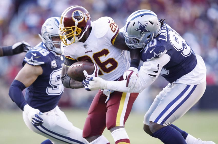 LANDOVER, MD - OCTOBER 21: Adrian Peterson #26 of the Washington Redskins gets tackled for a loss of yards by DeMarcus Lawrence #90 of the Dallas Cowboys in the first quarter of the game at FedExField on October 21, 2018 in Landover, Maryland. (Photo by Joe Robbins/Getty Images)