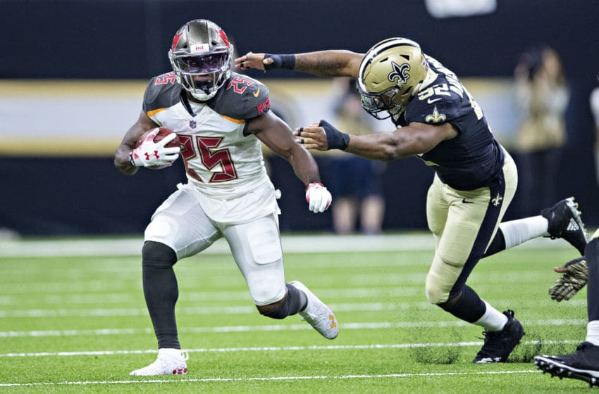 NEW ORLEANS, LA - SEPTEMBER 9: Peyton Barber #25 of the Tampa Bay Buccaneers runs the ball past the out stretch arms of Marcus Davenport #92 of the New Orleans Saints at Mercedes-Benz Superdome on September 9, 2018 in New Orleans, Louisiana. The Buccaneers defeated the Saints 48-40. (Photo by Wesley Hitt/Getty Images)