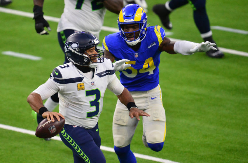 Nov 15, 2020; Inglewood, California, USA; Seattle Seahawks quarterback Russell Wilson (3) moves out to pass as Los Angeles Rams outside linebacker Leonard Floyd (54) moves in during the second half at SoFi Stadium. Mandatory Credit: Gary A. Vasquez-USA TODAY Sports