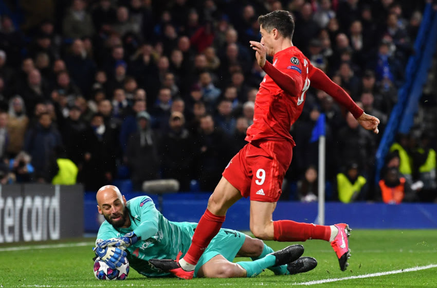 Chelsea's Argentinian goalkeeper Willy Caballero (L) saves at the feet of Bayern Munich's Polish striker Robert Lewandowski (R) during the UEFA Champion's League round of 16 first leg football match between Chelsea and Bayern Munich at Stamford Bridge in London on February 25, 2020. (Photo by Ben STANSALL / AFP) (Photo by BEN STANSALL/AFP via Getty Images)
