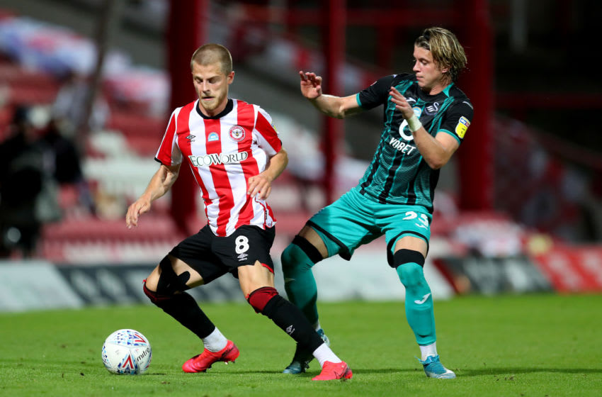 BRENTFORD, ENGLAND - JULY 29: Mathias Jensen (L) of Brentford challenges Conor Gallagher of Swansea during the Sky Bet Championship Play Off Semi-final 2nd Leg match between Brentford and Swansea City at Griffin Park on July 29, 2020 in Brentford, England. Football Stadiums around Europe remain empty due to the Coronavirus Pandemic as Government social distancing laws prohibit fans inside venues resulting in all fixtures being played behind closed doors. (Photo by Catherine Ivill/Getty Images)