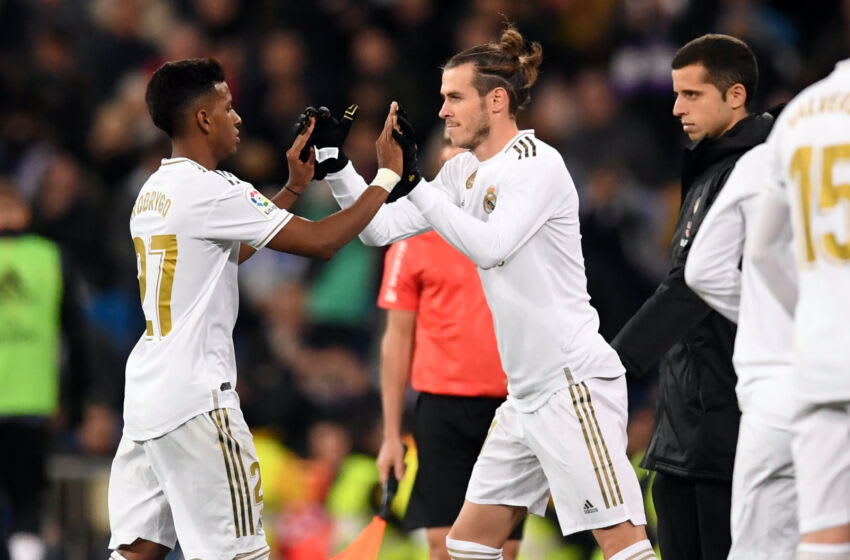 Real Madrid's Welsh forward Gareth Bale (R) shakes hands with Real Madrid's Brazilian forward Rodrygo during the Spanish league football match Real Madrid CF against Real Sociedad at the Santiago Bernabeu stadium in Madrid on November 23, 2019. (Photo by PIERRE-PHILIPPE MARCOU / AFP) (Photo by PIERRE-PHILIPPE MARCOU/AFP via Getty Images)