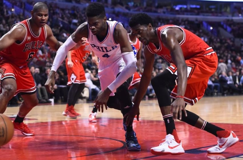 Apr 13, 2016; Chicago, IL, USA; Philadelphia 76ers forward Nerlens Noel (4) and Chicago Bulls guard Justin Holiday (7) attempt to get a loose ball during the second half at the United Center. Mandatory Credit: Mike DiNovo-USA TODAY Sports
