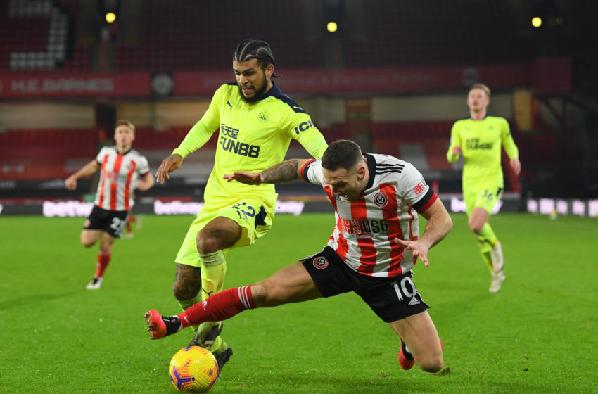 SHEFFIELD, ENGLAND - JANUARY 12: Billy Sharp of Sheffield United (r) is challenged by DeAndre Yedlin during the Premier League match between Sheffield United and Newcastle United at Bramall Lane on January 12, 2021 in Sheffield, England. Sporting stadiums around England remain under strict restrictions due to the Coronavirus Pandemic as Government social distancing laws prohibit fans inside venues resulting in games being played behind closed doors. (Photo by Stu Forster/Getty Images)