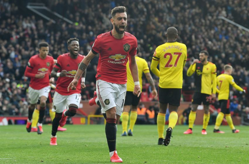 Manchester United's Portuguese midfielder Bruno Fernandes (C) celebrates scoring the opening goal from the penalty spot during the English Premier League football match between Manchester United and Watford at Old Trafford in Manchester, north west England, on February 23, 2020. (Photo by Paul ELLIS / AFP) / RESTRICTED TO EDITORIAL USE. No use with unauthorized audio, video, data, fixture lists, club/league logos or 'live' services. Online in-match use limited to 120 images. An additional 40 images may be used in extra time. No video emulation. Social media in-match use limited to 120 images. An additional 40 images may be used in extra time. No use in betting publications, games or single club/league/player publications. / (Photo by PAUL ELLIS/AFP via Getty Images)
