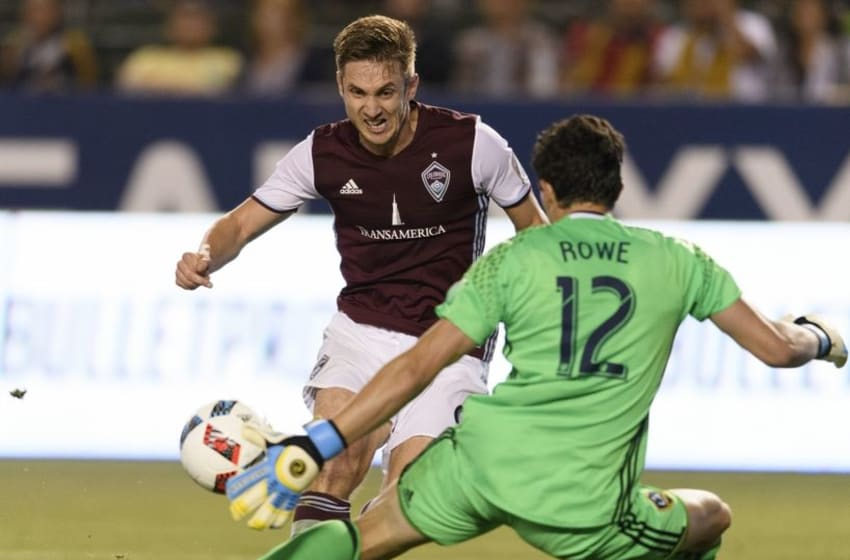 Jun 22, 2016; Carson, CA, USA; Colorado Rapids forward Kevin Doyle (back) attempts a shot in front of LA Galaxy goalkeeper Brian Rowe (12) during the second half at StubHub Center. The game ended in a draw with a final score of 0-0. Mandatory Credit: Kelvin Kuo-USA TODAY Sports