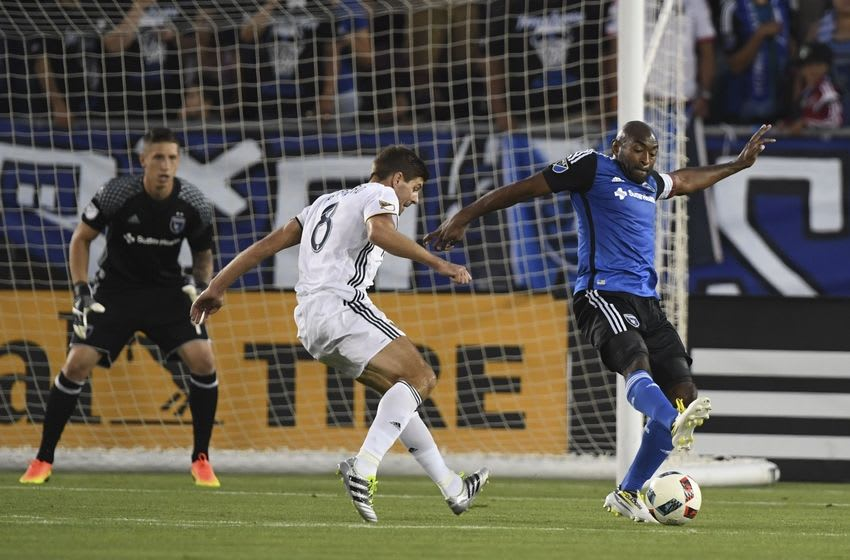 June 25, 2016; Stanford, CA, USA; San Jose Earthquakes defender Marvell Wynne (4, right) kicks the ball against Los Angeles Galaxy midfielder Steven Gerrard (8) during the second half at Stanford Stadium. Mandatory Credit: Kyle Terada-USA TODAY Sports