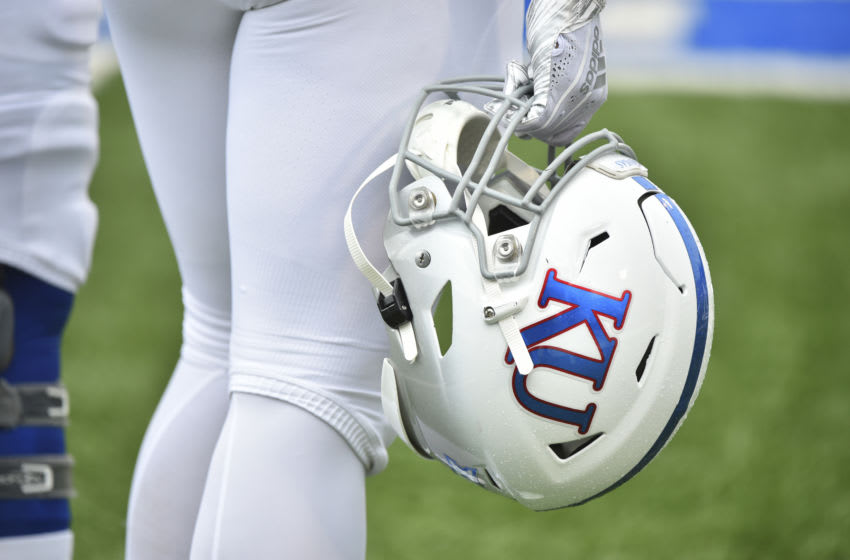 A Kansas football player holds his helmet at Memorial Stadium on September 21, 2019. (Photo by Ed Zurga/Getty Images)