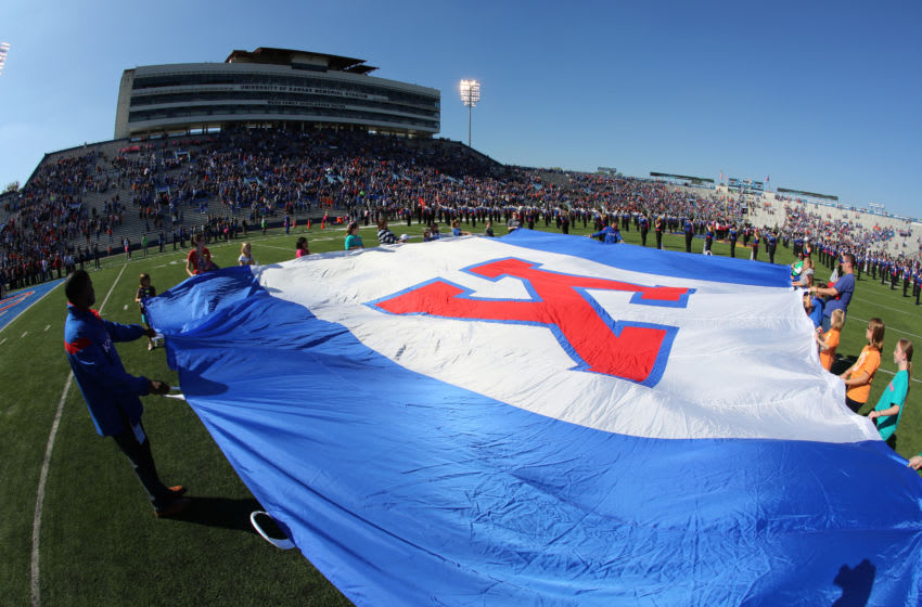 Kansas football fans hold a University of Kansas school flag during the playing of the nation anthem prior to a game. (Photo by Ed Zurga/Getty Images)
