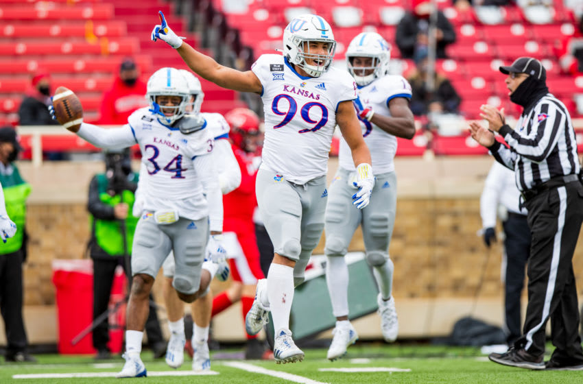LUBBOCK, TEXAS - DECEMBER 05: Defensive lineman Malcom Lee #99 of the Kansas Jayhawks celebrates after a fumble recovery by Nate Betts #34 during the second half of the college football game against the Texas Tech Red Raiders at Jones AT&T Stadium on December 05, 2020 in Lubbock, Texas. (Photo by John E. Moore III/Getty Images)