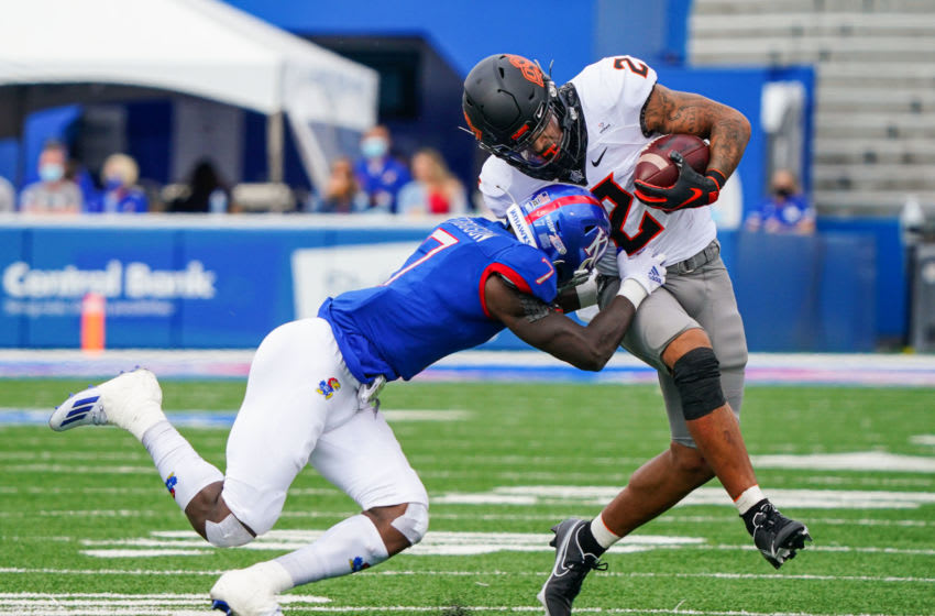 Cowboys wide receiver Tylan Wallace runs against Kansas football safety Davon Ferguson. Mandatory Credit: Jay Biggerstaff-USA TODAY Sports