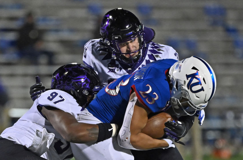Nov 28, 2020; Lawrence, Kansas, USA; TCU Horned Frogs defensive tackle Earl Barquet (97) and linebacker Garret Wallow (30) tackle running back Amauri Pesek-Hickson (23)during the third quarter at David Booth Kansas Memorial Stadium. Mandatory Credit: Peter Aiken-USA TODAY Sports