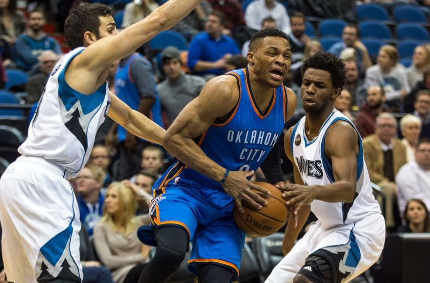 Jan 12, 2016; Minneapolis, MN, USA; Oklahoma City Thunder guard Russell Westbrook (0) dribbles past Minnesota Timberwolves guard Andrew Wiggins (22) and guard Ricky Rubio (9) during the first quarter at Target Center. Mandatory Credit: Brace Hemmelgarn-USA TODAY Sports