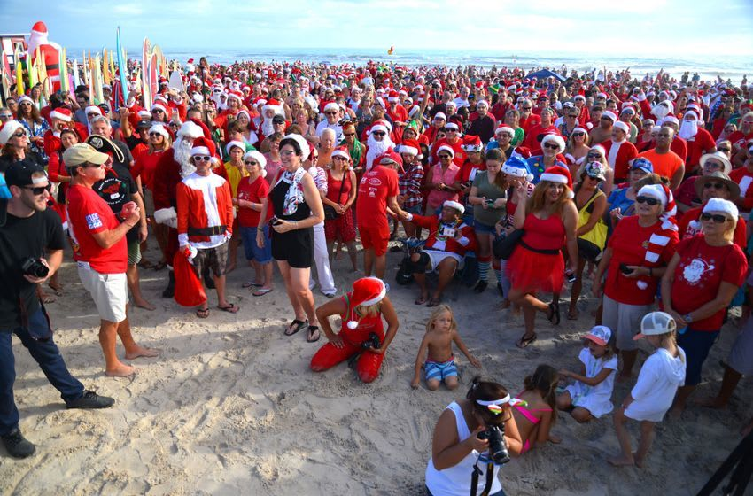 Dec 24, 2016; Cocoa Beach, FL, USA; Thousands turn out on Christmas Eve morning in Cocoa Beach to watch hundreds of surfing Santas hit the waves. The event started eight years ago when George Trosset went surfing in a Santa suit with his son and daughter-in-law. The event has ballooned into a major Christmas event supporting Grind for Life and the Surf Museum. Mandatory Credit: Malcolm Denemark/Florida Today via USA TODAY NETWORK