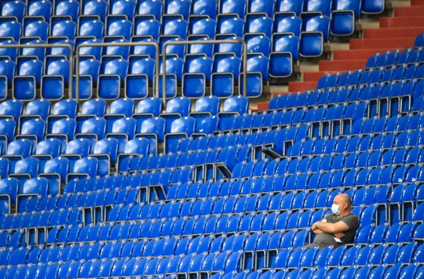 OKC Thunder: A man wearing a protective facemask sits in the empty stadium (Photo by WOLFGANG RATTAY/POOL/AFP via Getty Images)