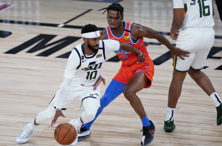 LAKE BUENA VISTA, FLORIDA - AUGUST 01: Mike Conley #10 of the Utah Jazz drives into Shai Gilgeous-Alexander #2 of the Oklahoma City Thunder during the second half of an NBA basketball game on August 1, 2020 in Lake Buena Vista, Florida. NOTE TO USER: User expressly acknowledges and agrees that, by downloading and or using this photograph, User is consenting to the terms and conditions of the Getty Images License Agreement. (Photo by Ashley Landis - Pool/Getty Images)