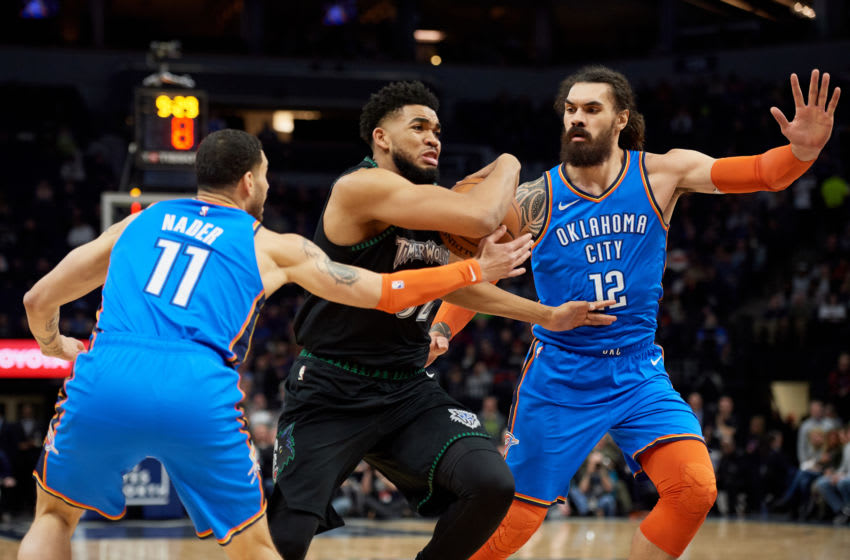 MARCH 05: Steven Adams #12 and Abdel Nader #11 of the OKC Thunder defend Karl-Anthony Towns #32 of the Minnesota Timberwolves as he drives to the basket. (Photo by Hannah Foslien/Getty Images)