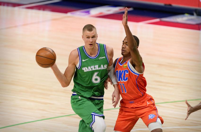 Mavericks center Kristaps Porzingis (6) passes the ball by OKC Thunder guard Theo Maledon : Jerome Miron-USA TODAY Sports