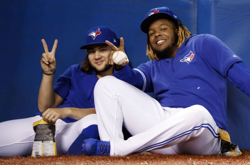Bo Bichette #11 and Vladimir Guerrero Jr. #27 of the Toronto Blue Jays sit in the dugout during the ninth inning of their MLB game against the Tampa Bay Rays at Rogers Centre. (Photo by Cole Burston/Getty Images)