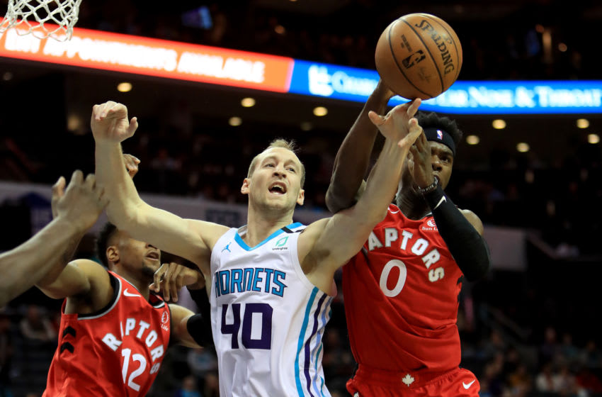 Cody Zeller #40 of the Charlotte Hornets tries to grab the ball from teammates Oshae Brissett #12 and Terence Davis #0 of the Toronto Raptors during their game at Spectrum Center. (Photo by Streeter Lecka/Getty Images)