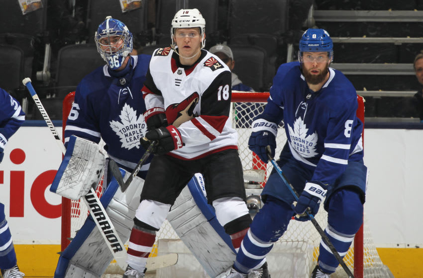 Christian Dvorak #18 of the Arizona Coyotes looks for a puck to tip between Jack Campbell #36 and Jake Muzzin #8 of the Toronto Maple Leafs during an NHL game at Scotiabank Arena. (Photo by Claus Andersen/Getty Images)