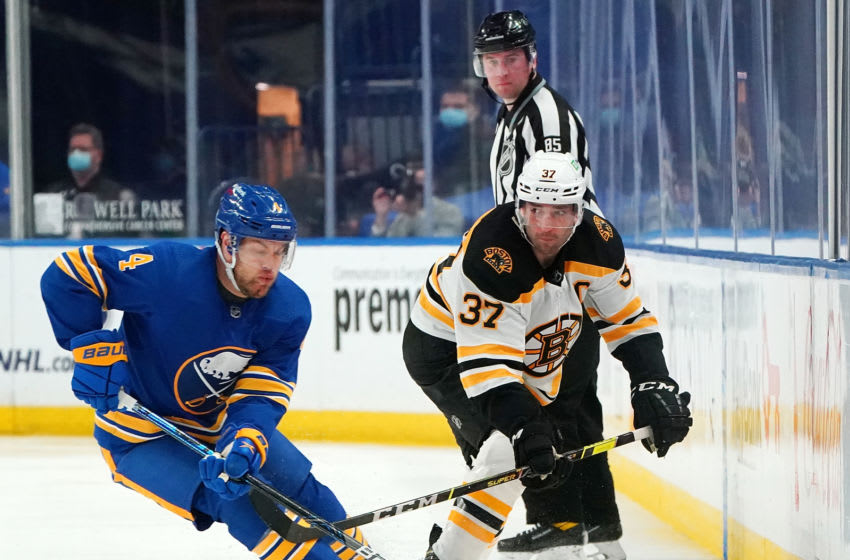 Patrice Bergeron #37 of the Boston Bruins flips the puck past Taylor Hall #4 of the Buffalo Sabres. (Photo by Kevin Hoffman/Getty Images)