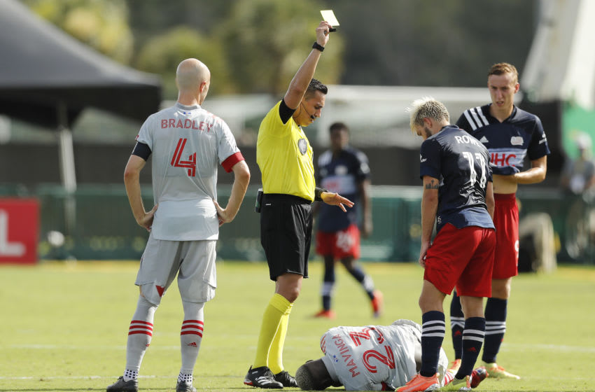 Referee Jair Marrufo gives a yellow card to Kelyn Rowe of New England Revolution after tripping Chris Mavinga of Toronto FC. (Photo by Michael Reaves/Getty Images)