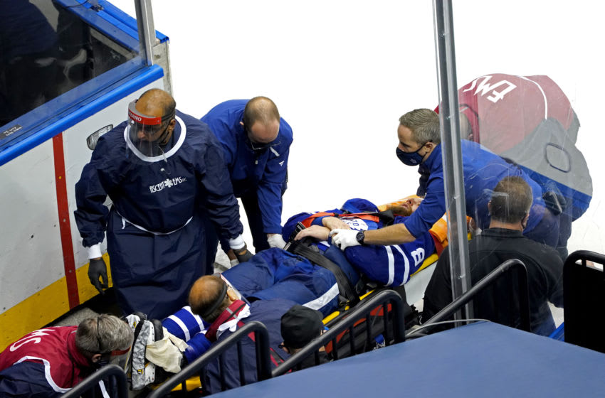 Jake Muzzin of the Toronto Maple Leafs is carried off the ice. (Photo by Andre Ringuette/Freestyle Photo/Getty Images)