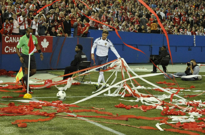 David Beckham #23 of the Los Angeles Galaxy removes streamers strewn on the pitch during CONCACAF Champions League game action against the Toronto FC. (Photo by Brad White/Getty Images)