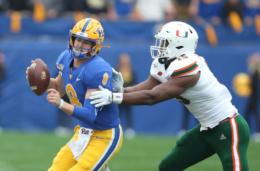 Oct 26, 2019; Pittsburgh, PA, USA; Pittsburgh Panthers quarterback Kenny Pickett (8) is chased by Miami Hurricanes defensive lineman Gregory Rousseau (15) during the first quarter at Heinz Field. Mandatory Credit: Charles LeClaire-USA TODAY Sports
