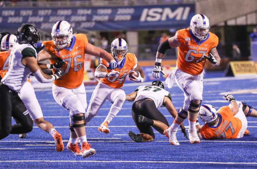 BOISE, ID - OCTOBER 12: Running back Robert Mahone #34 runs behind blocks from offensive lineman Ezra Cleveland #76 and offensive lineman Garrett Larson #67 of the Boise State Broncos during second half action against the Hawaii Rainbow Warriors on October 12, 2019 at Albertsons Stadium in Boise, Idaho. Boise State won the game 59-37. (Photo by Loren Orr/Getty Images)