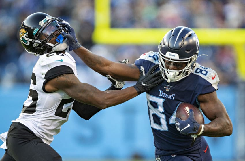 NASHVILLE, TN - NOVEMBER 24: Corey Davis #84 of the Tennessee Titans runs the ball and stiff arms Jarrod Wilson #26 of the Jacksonville Jaguars during the first half at Nissan Stadium on November 24, 2019 in Nashville, Tennessee. The Titans defeated the Jaguars 42-20. (Photo by Wesley Hitt/Getty Images)
