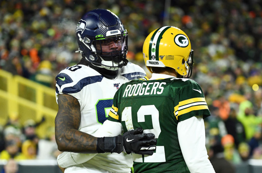 GREEN BAY, WISCONSIN - JANUARY 12: Jadeveon Clowney #90 of the Seattle Seahawks stands with Aaron Rodgers #12 of the Green Bay Packers during the first half in the NFC Divisional Playoff game at Lambeau Field on January 12, 2020 in Green Bay, Wisconsin. (Photo by Stacy Revere/Getty Images)