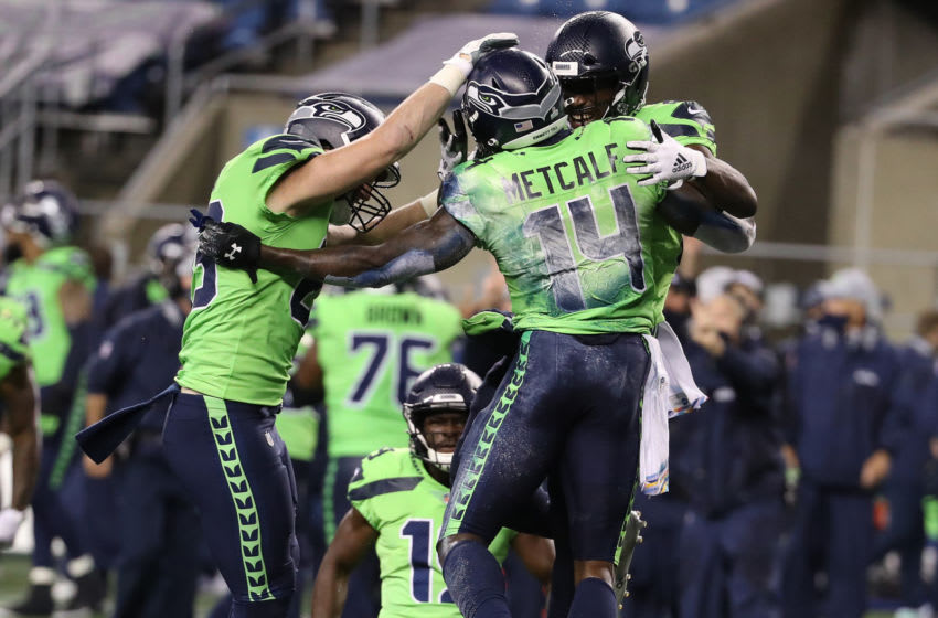 SEATTLE, WASHINGTON - OCTOBER 11: DK Metcalf #14 of the Seattle Seahawks is congratulated by teammates after scoring the game winning touchdown against the Minnesota Vikings during the fourth quarter at CenturyLink Field on October 11, 2020 in Seattle, Washington. (Photo by Abbie Parr/Getty Images)