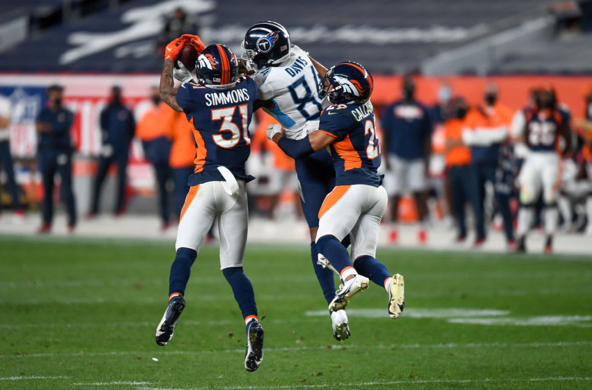DENVER, CO - SEPTEMBER 14: Corey Davis #84 of the Tennessee Titans makes a contested catch as Justin Simmons #31 and Bryce Callahan #29 of the Denver Broncos cover the play in the third quarter of a game at Empower Field at Mile High on September 14, 2020 in Denver, Colorado. (Photo by Dustin Bradford/Getty Images)