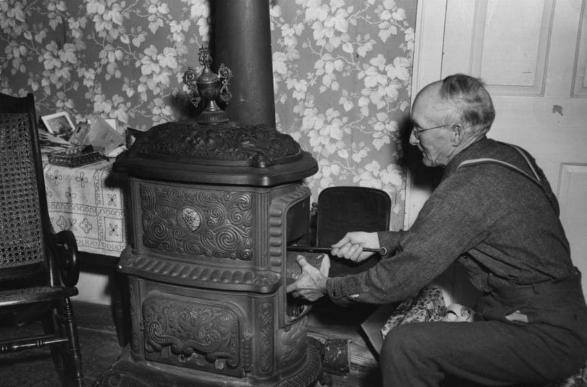 circa 1950: An elderly American gentleman getting his old fashioned 'shunck' stove burning. (Photo by Three Lions/Getty Images)