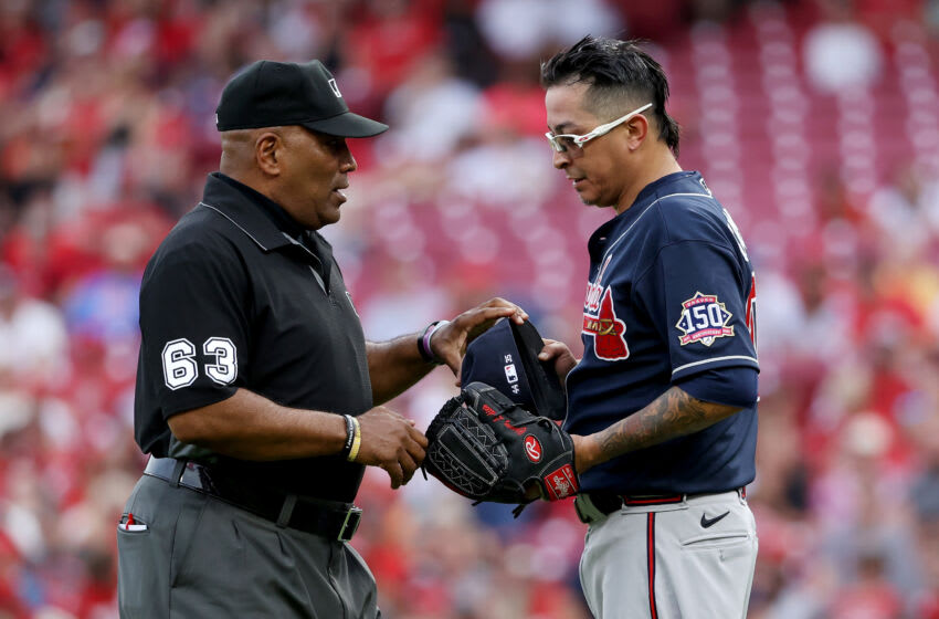 CINCINNATI, OHIO - JUNE 24: Umpire Laz Diaz inspects the hat of glove of Jesse Chavez #60 of the Atlanta Braves after the first inning at Great American Ball Park on June 24, 2021 in Cincinnati, Ohio. (Photo by Dylan Buell/Getty Images)