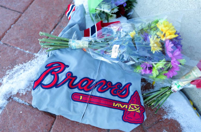 An Atlanta Braves jacket, flowers, and mementos are left at a makeshift memorial in front of the Henry Aaron statue at American Family Field Saturday. Aaron Statue 06327 (No photo credit reported)