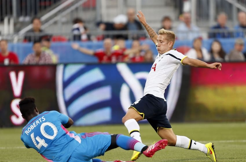Jul 23, 2014; Toronto, Ontario, Canada; Toronto FC goalkeeper Quillan Roberts (40) makes a save on Tottenham Hotspur midfielder Lewis Holtby (14) at BMO Field. Tottenham defeated Toronto 3-2. Mandatory Credit: John E. Sokolowski-USA TODAY Sports