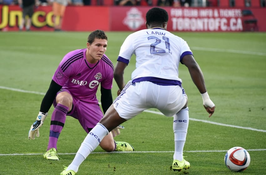 Aug 5, 2015; Toronto, Ontario, CAN; Toronto FC goalkeeper Joe Bendik (12) blocks a scoring attempt by Orlando City forward Cyle Larin (21) in the first half at BMO Field. Mandatory Credit: Dan Hamilton-USA TODAY Sports