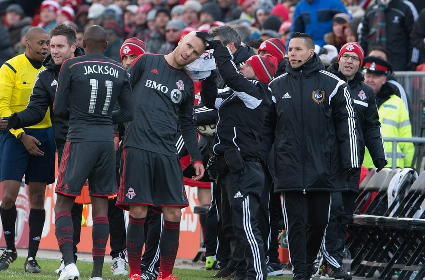Mar 22, 2014; Toronto, Ontario, CAN; Toronto FC midfielder Michael Bradley (4) is attended to by the Toronto FC training staff after a collision with D.C. United midfielder Davy Arnaud (not pictured) during the second half at BMO Field. Toronto FC won 1-0. Mandatory Credit: Nick Turchiaro-USA TODAY Sports