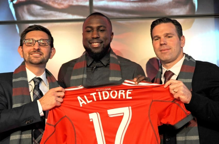 Jan 16, 2015; Toronto, ON, Canada; Toronto FC striker Jozy Altidore is presented with his Toronto FC team jersey by club general manager Tim Bezbatchenko (left) and head coach Greg Vanney (right) during a media conference at Air Canada Centre. Mandatory Credit: Dan Hamilton-USA TODAY Sports