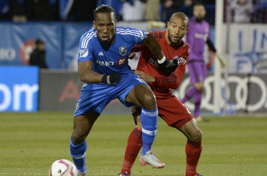 Oct 29, 2015; Montreal, Quebec, CAN; Montreal Impact forward Didier Drogba (11) plays the ball and Toronto FC defender Justin Morrow (2) defends during the second half of a knockout round match of the 2015 MLS Cup Playoffs at Stade Saputo. Mandatory Credit: Eric Bolte-USA TODAY Sports