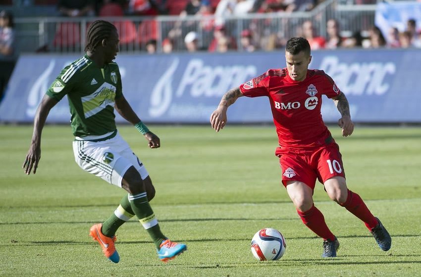 May 23, 2015; Toronto, Ontario, CAN; Toronto FC midfielder Sebastian Giovinco (10) battles for a ball with Portland Timbers midfielder Diego Chara (21) during the second half in a game at BMO Field. Toronto FC won 1-0. Mandatory Credit: Nick Turchiaro-USA TODAY Sports