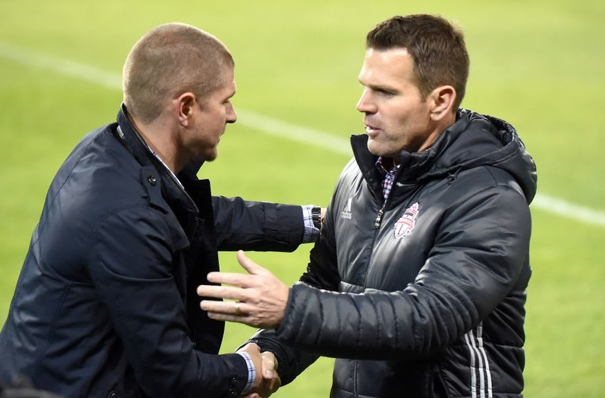 May 14, 2016; Toronto, Ontario, CAN; Toronto FC head coach Greg Vanney (right) shakes hands with Vancouver Whitecaps head coach Carl Robinson after the Whitecaps 4-3 win at BMO Field. Mandatory Credit: Dan Hamilton-USA TODAY Sports